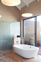 Free-standing bathtub on elegant tiled floor next to terrace doors and shower screen