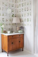 Table lamp on cabinet in corner of room with white wainscoting and botanical wallpaper