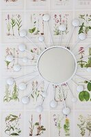 Sunburst mirror on wallpaper with botanical pattern