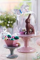 Easter sweets on china cake stands under glass covers