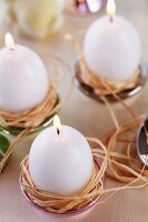 Egg-shaped candles in raffia nests in small dishes used as candle holders