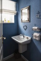 Washbasin and towel rack mounted on blue-painted bathroom wall