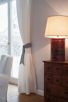 Table lamp hand-crafted from vintage coffee can on chest of drawers next to draped curtains on French windows