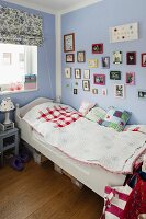 Single bed with white-painted wooden frame below framed pictures on lilac wall in corner of child's bedroom