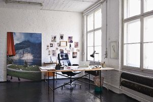 Eiermann table and executive chair in loft apartment; landscape photo and mood board in background