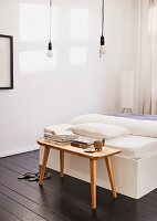 Bedroom with dark wood floor, pendant lamp with pull switch and wooden bench used as bedside table for DIY bed