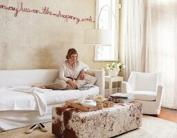 Text artwork on sand-coloured wall above sofa with white loose cover and ottoman with animal-skin cover; woman reading on sofa