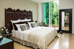 Double bed, bedspread, stacked scatter cushions and Indian wooden screen against sand-coloured wall; glass sliding doors with view of garden in background