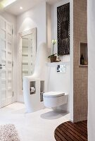 An organically shaped partition wall next to the toilet with spaces for paper and toilet brush in a cosy spa bathroom