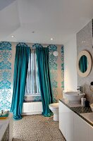 Bathroom with floor-length curtains on window, floral wallpaper and washstand with countertop basins to one side