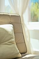 Detail of easy chair backrest with pale, button-tufted leather cover and cushion