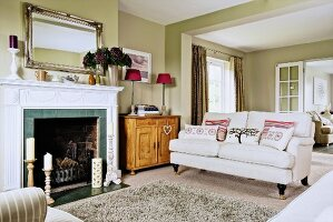 Fireplace with white surround and couch in open-plan interior with pale green walls
