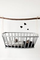 Hedgehog toy and knitted ball in dolls' crib hung from wooden pole; black paper leaf silhouettes on wall