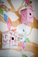 Painted nesting boxes hung on wall with tree mural