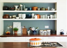 Crockery on white shelves in grey-painted niche