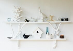 Various china birds on white wall-mounted shelves on white wall