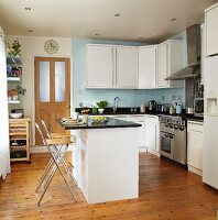 Modern, white fitted kitchen with black worksurfaces, pale blue tiled splashback and central breakfast bar