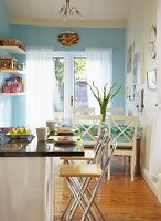 Kitchen with breakfast bar and dining area in front of wall painted pale blue