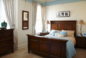Traditional bedroom with accessories and pale blue frieze combined with dark wooden furniture
