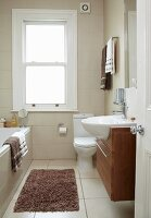 Narrow, traditional bathroom in renovated period building; modern washstand with sink protruding over floating base unit