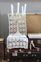 Open, vintage suitcase, candelabra and white crocheted doily