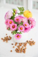 Pink asters and yellow dahlia in white vase and hazelnuts scattered on surface