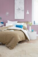 Spotted bed linen on a double bed in a romantically designed bedroom with lilac painted walls