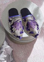 Oriental style slippers on top of a hatbox