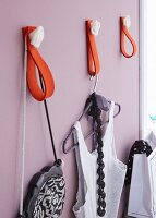 A homemade wardrobe made by attaching red felt loops to a lilac wall