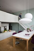 Dining area with modern table below white pendant lamps and free-standing kitchen counter below gallery
