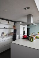 Woman in open-plan kitchen with free-standing counter and hob beneath extractor hood