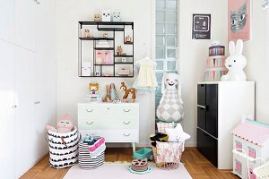 Toys in display case, storage bags on floor and decorative ornaments in nursery