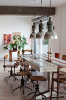 Retro swivel chair at long table below industrial pendant lamps in loft apartment