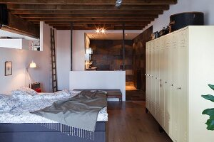 Bedroom with rustic, wood-beamed ceiling, white lockers and ensuite bathroom in loft apartment