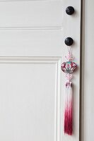 Ethnic-style pendant with tassel on doorknob of interior door