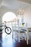 White dining table and refurbished second-hand chairs below chandelier; bicycle in background in front of open arched terrace doors