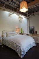 Double bed with ruffled bedspread in simple room with wicker pendant lampshade hung from corrugated metal ceiling