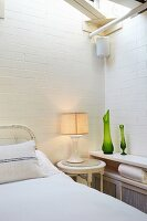 Lamp on bedside table between bed and green vases on shelf in corner of room with whitewashed brick walls
