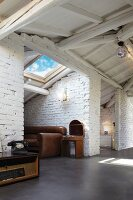 Niches with whitewashed brick walls under white-painted roof structure in loft apartment with vintage furnishings