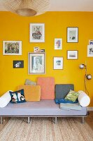 Various scatter cushions on simple couch below collection of pictures on yellow wall