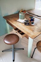 Retro stools around rustic kitchen table with legs painted pale mint green