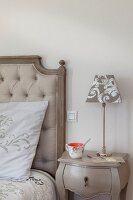 Pale grey bedside table next to bed with button-tufted headboard
