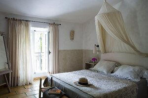 Soft natural shades in Provençal-style guest room with mosquito net and quilted bedspread (boutis) on double bed