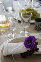 Blue anemone flower and floral napkin ring on linen napkin on charger plate next to rustic stemware