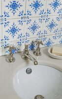 Traditional, blue and white tiles above stone washstand counter with old tap fittings and undermount sink