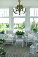 Chandelier above white, wicker chairs, set of matching tables and lanterns in conservatory with view into sunny park