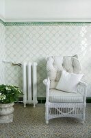 White wicker chair with pale, striped cushions against tiled dado in conservatory