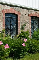 Stone façade with brick-framed windows on ground floor of old country manor behind row of flowering perennials