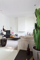 Sofa, black side table, coffee table and large potted cacti in elegant lounge area