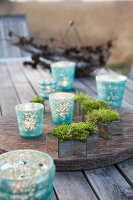 Moss in cutter with lanterns on a rustic wooden table
